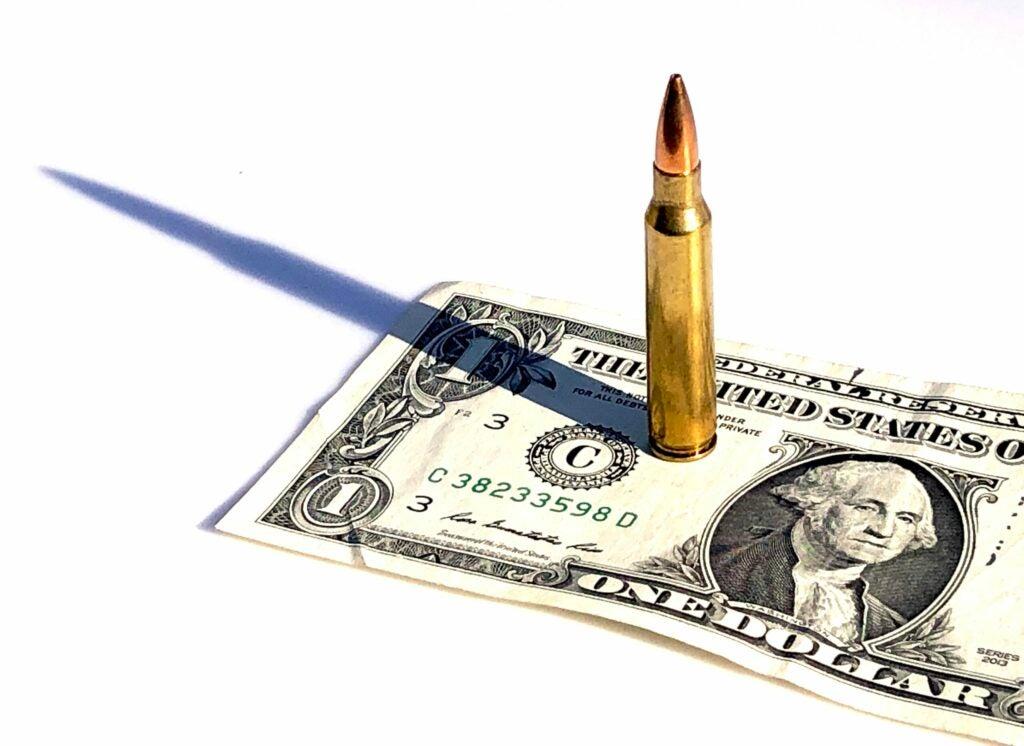 A .223 Remington cartridges standing on top of a dollar bill.