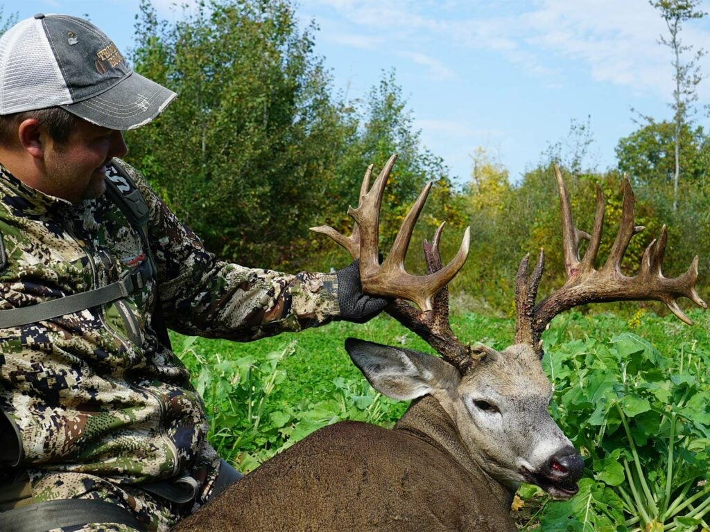 A hunter kneels beside a large whitetail deer and holds its head by the antlers.