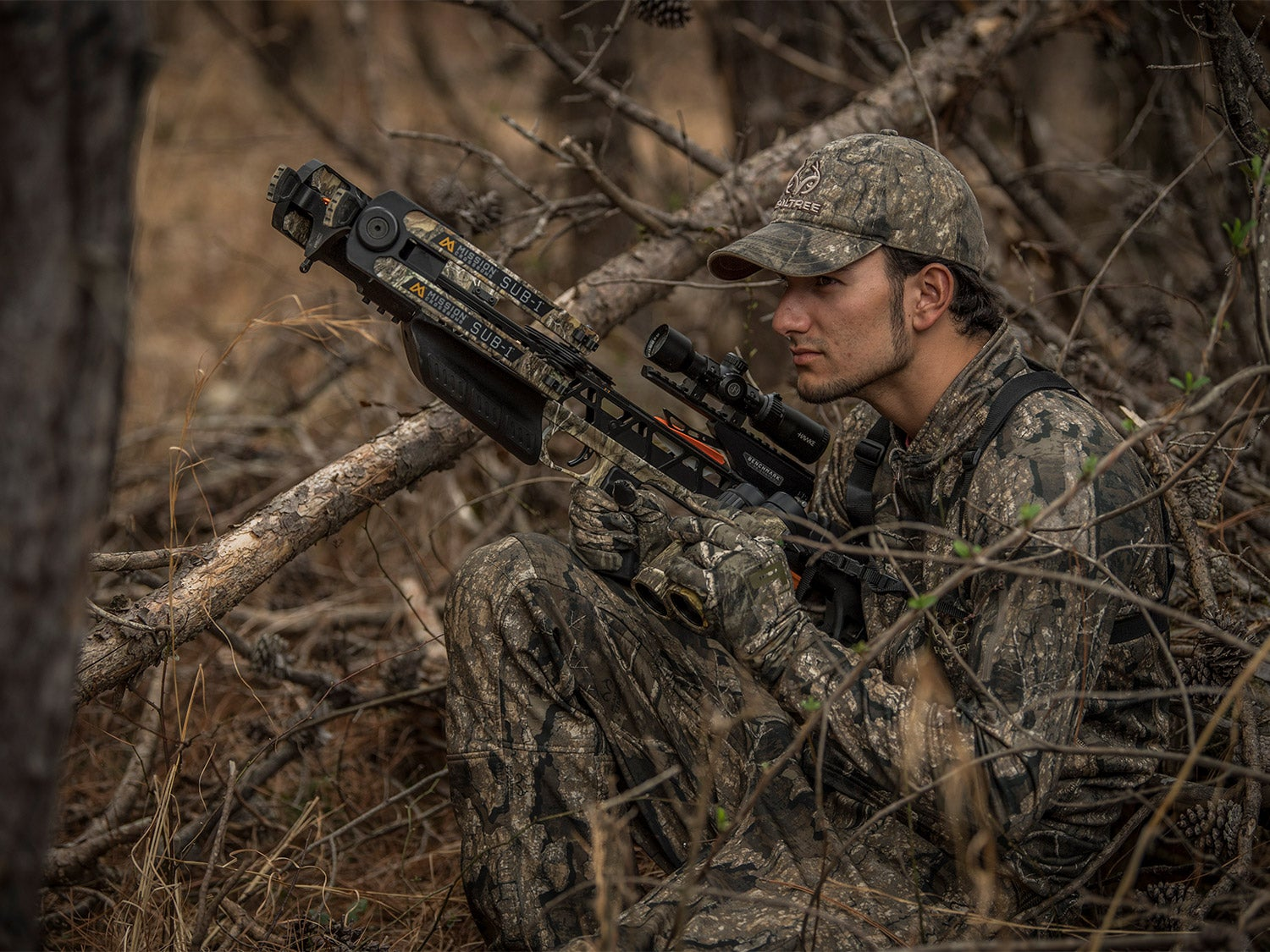 A hunter with a crossbow in a hunting blind.