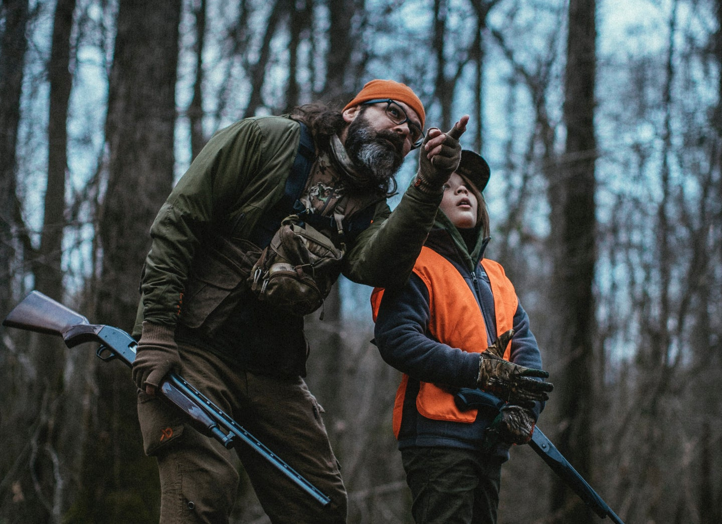 Father and son hunting for squirrels in the woods.