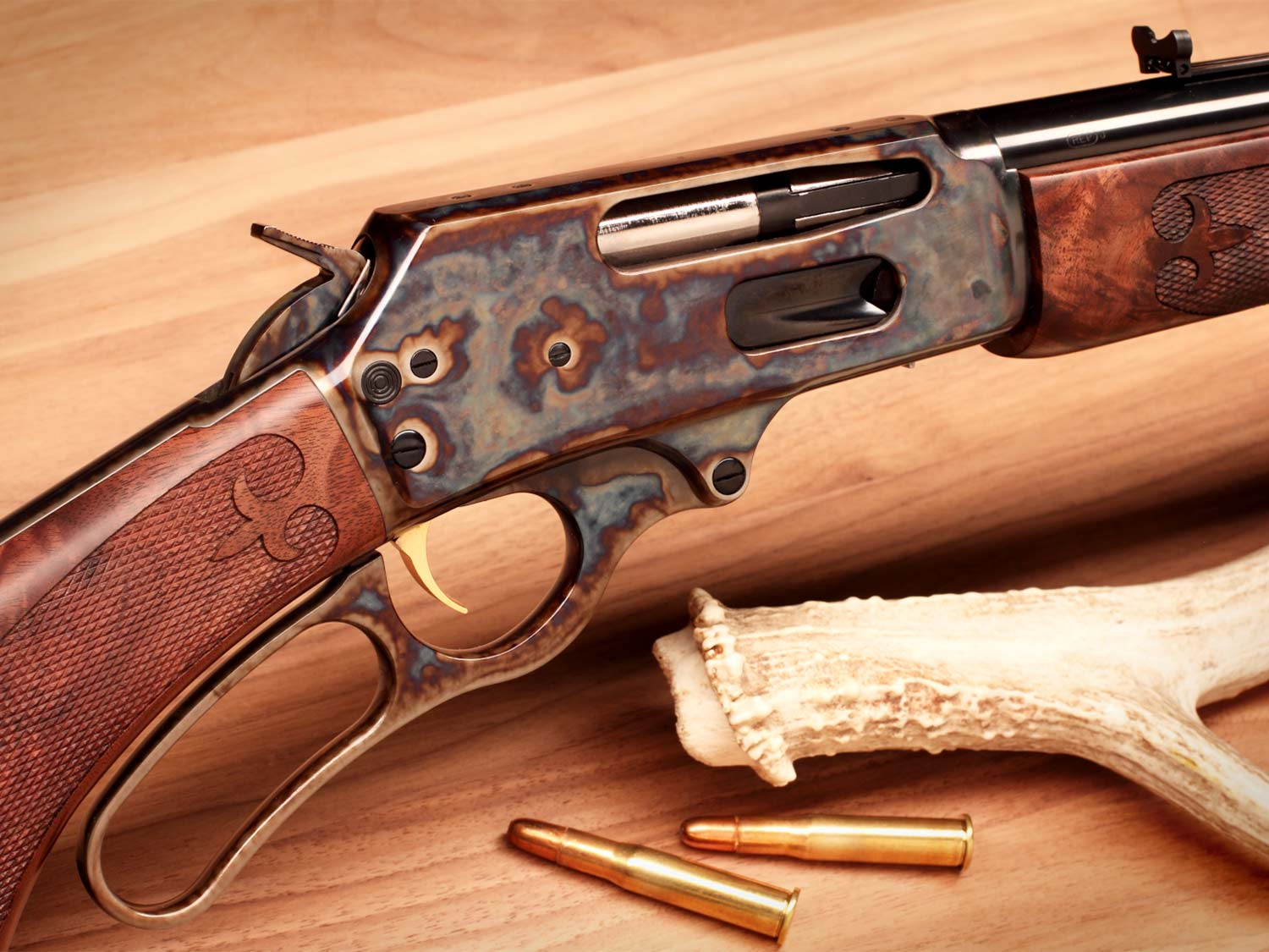 A close up image of a lever-action rifle on a wooden floor.