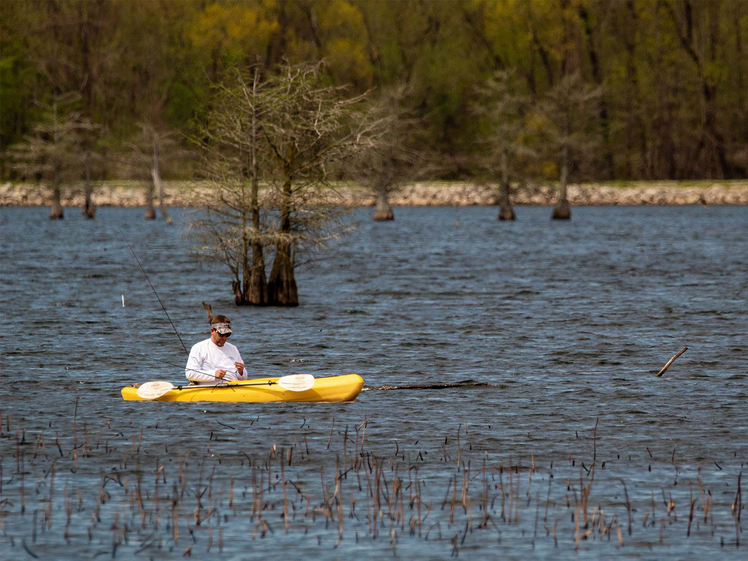 A man rides in a kayak across a lake using the best fishing motor.