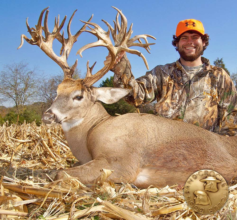 A hunter kneels beside a large whitetail buck.