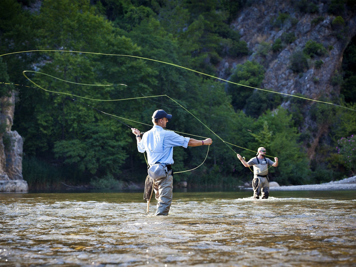Two men wade through a large stream with fly rods and fishing.