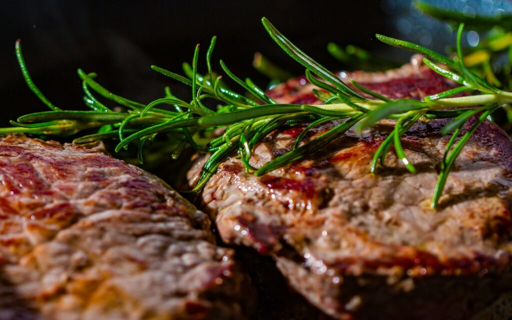 Fried meat in a pan with rosemary.