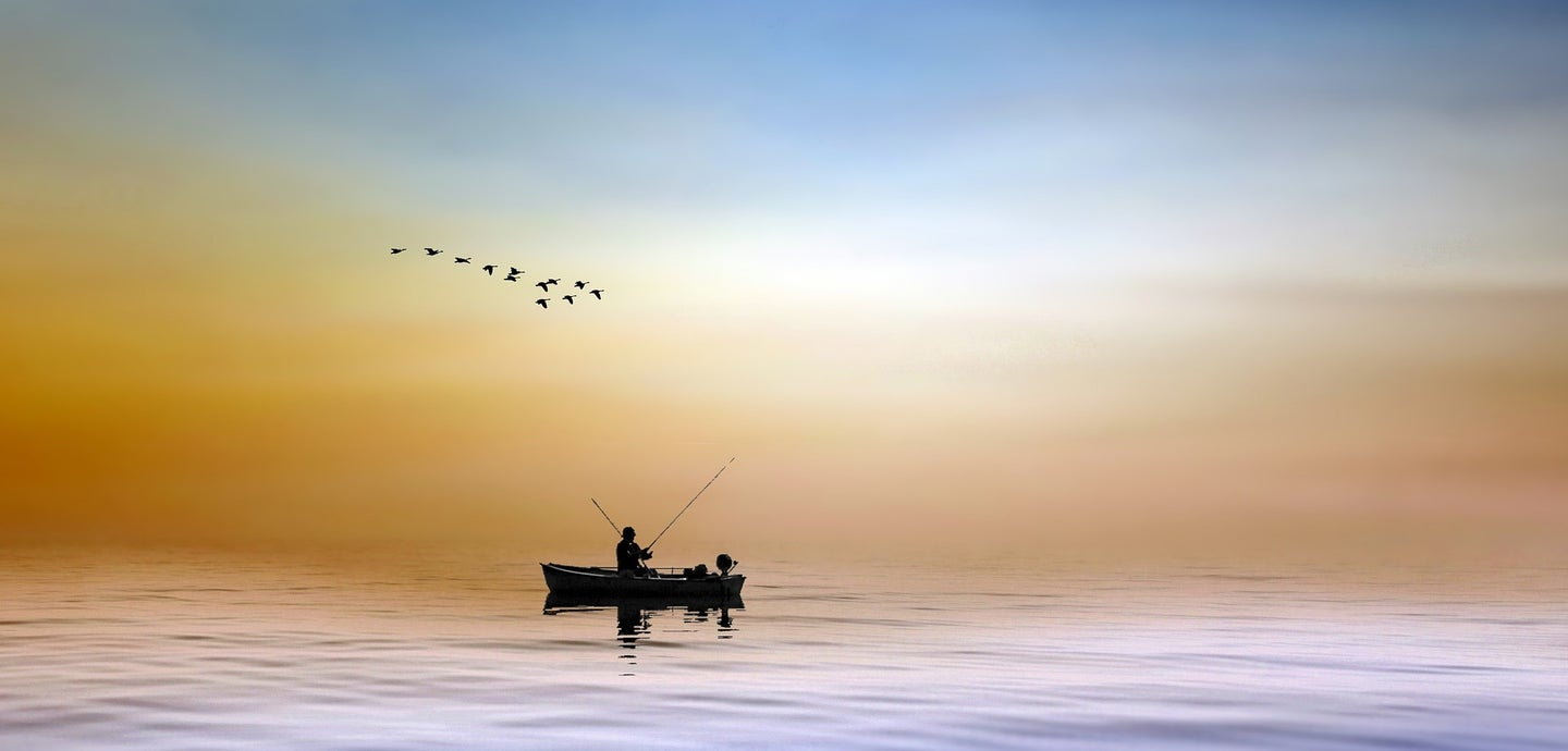 man fishing on a boat in the water