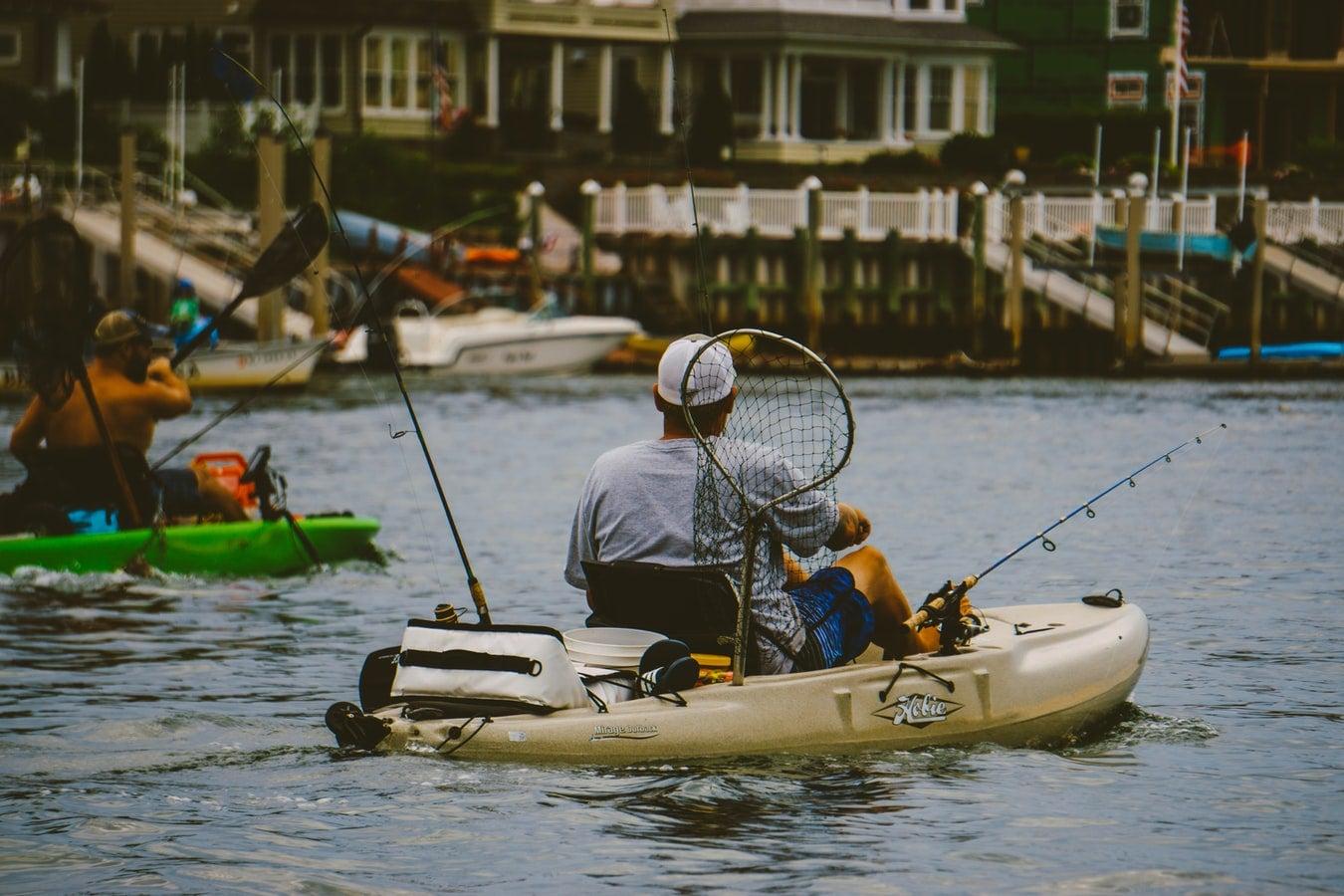 Two kayak anglers make their way down a river.