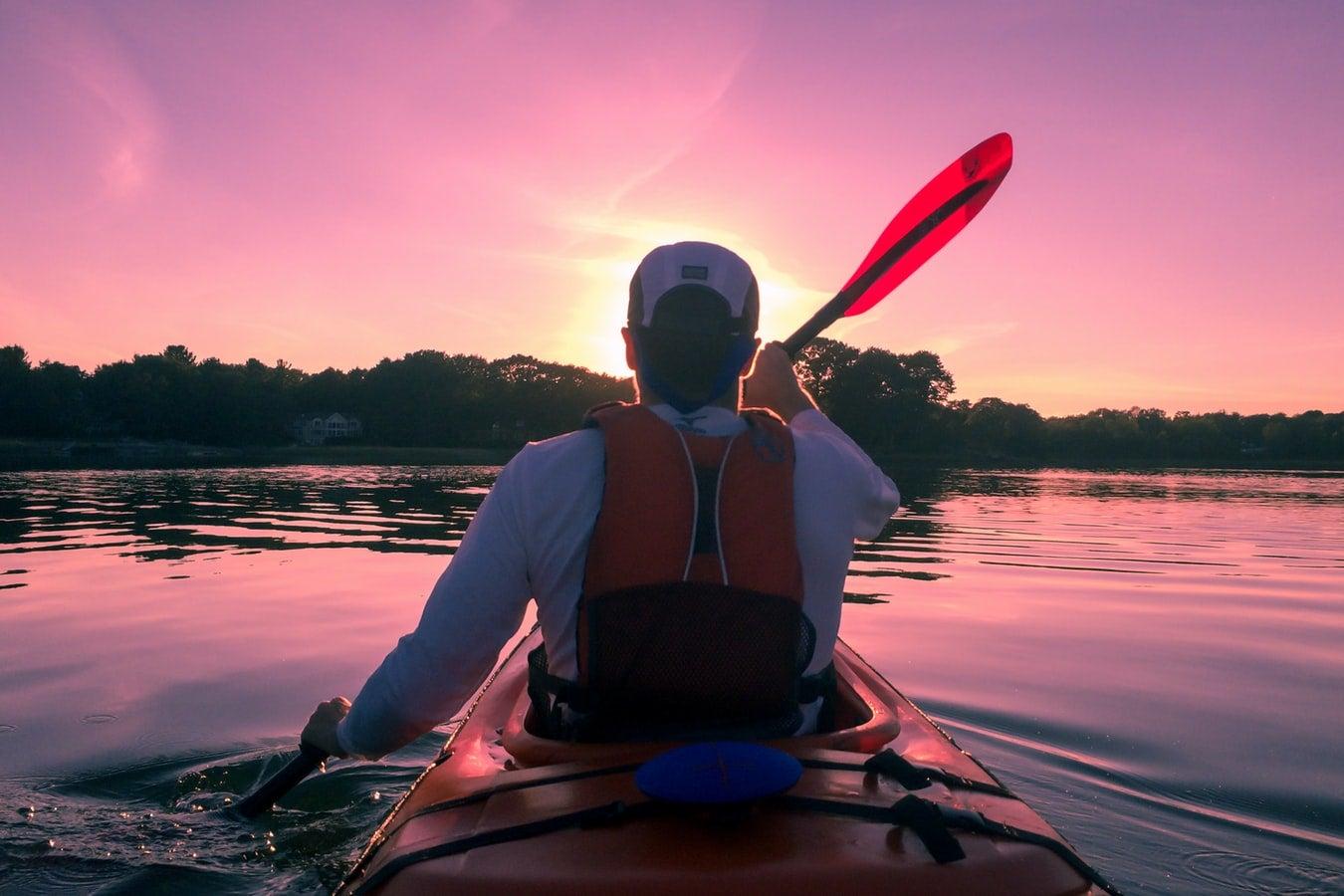 A man wearing a kayak fishing life vest paddles a kayak.
