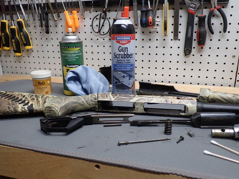 disassembled shotgun on work bench.