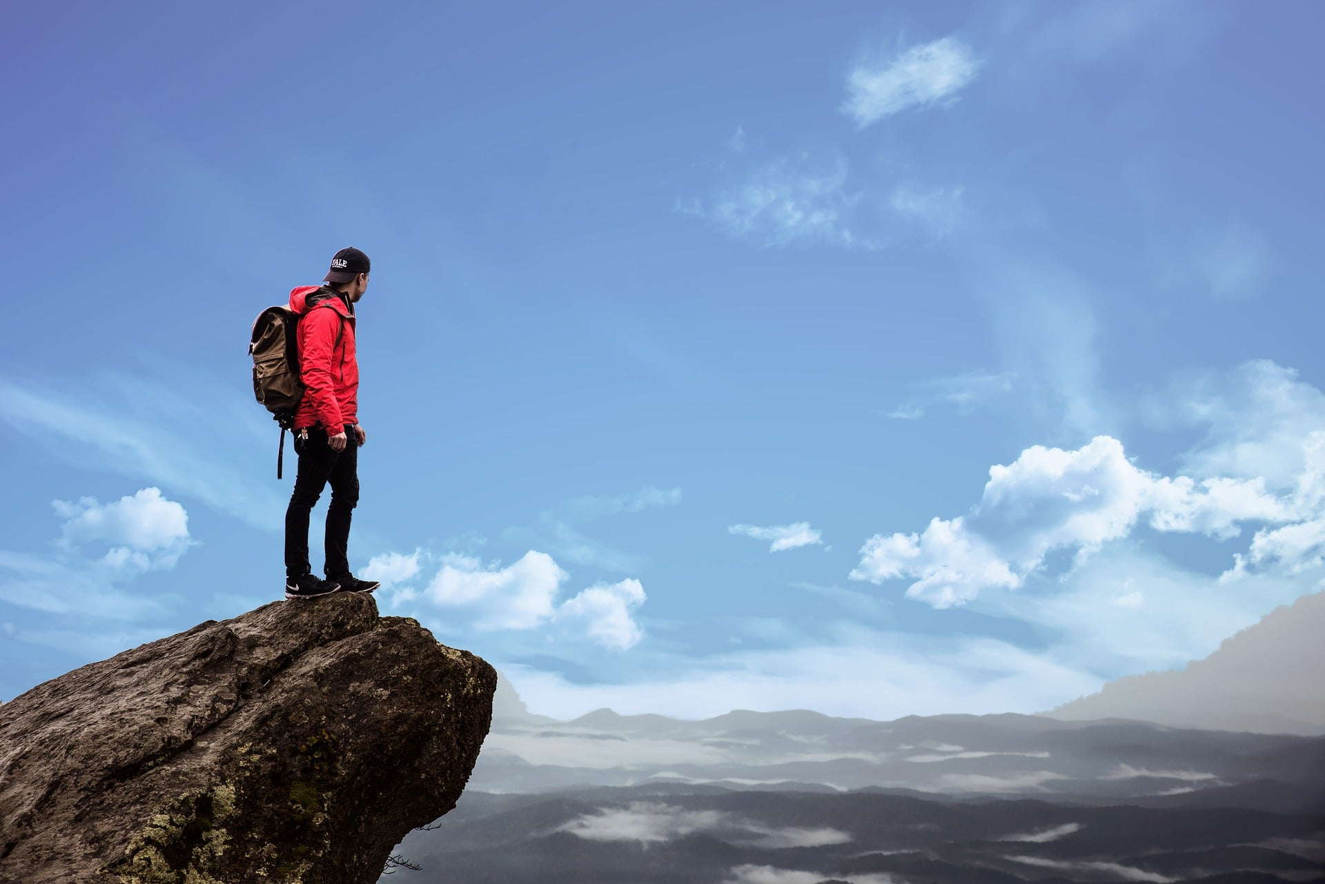 Man wearing backpack standing on high ledge