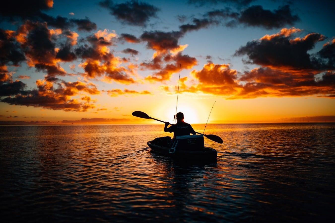 An angler paddles a kayak at dawn on a lake.