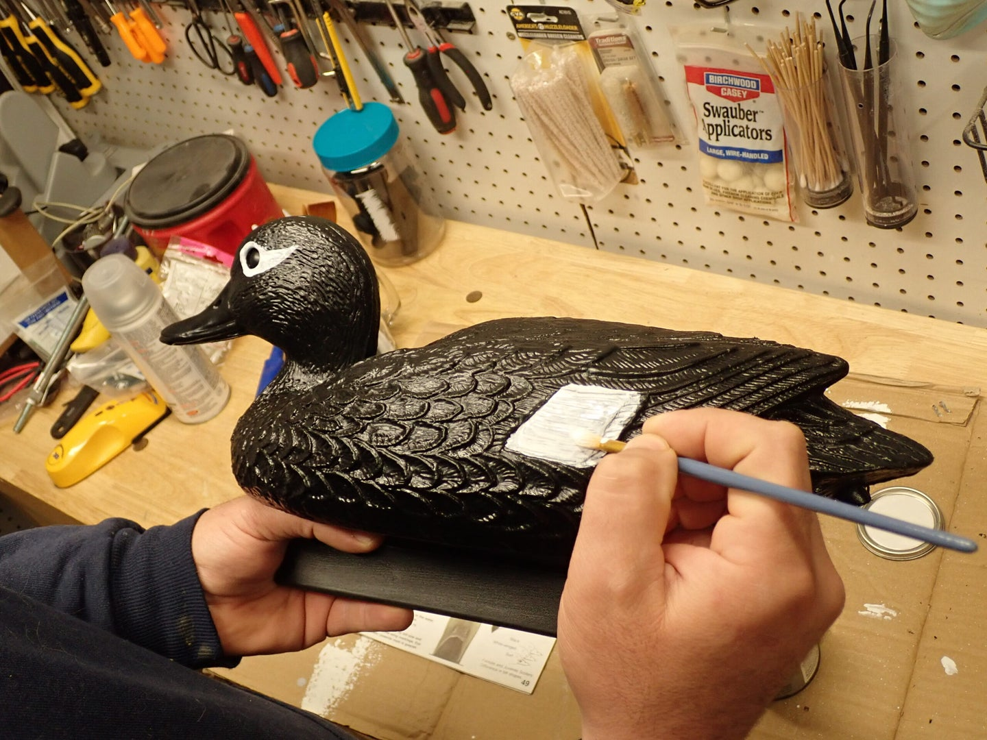 Painting duck decoy on a workbench.