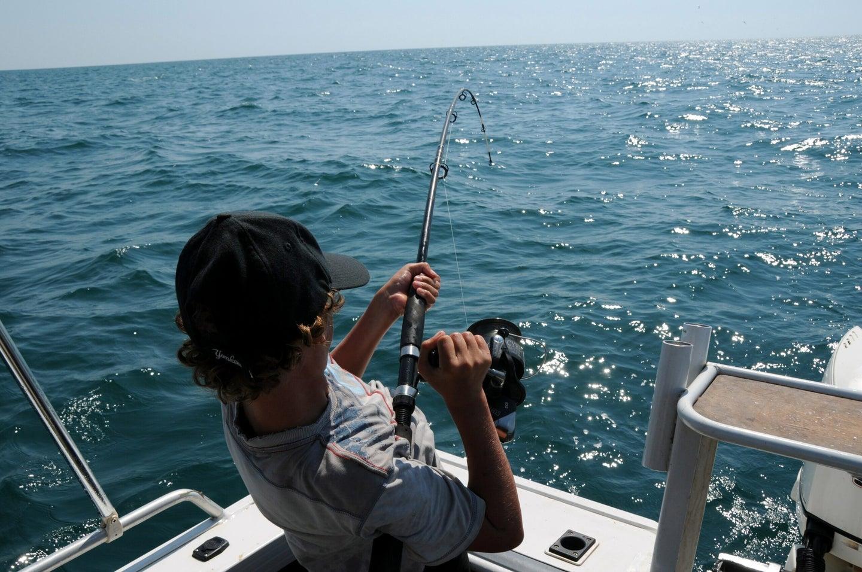 Man reeling in a fishing line.