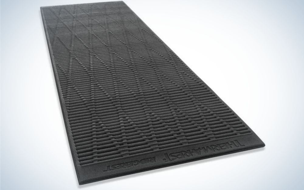 a black sleeping pad in a rectangular shape and with a surface designed with small rhombuses.