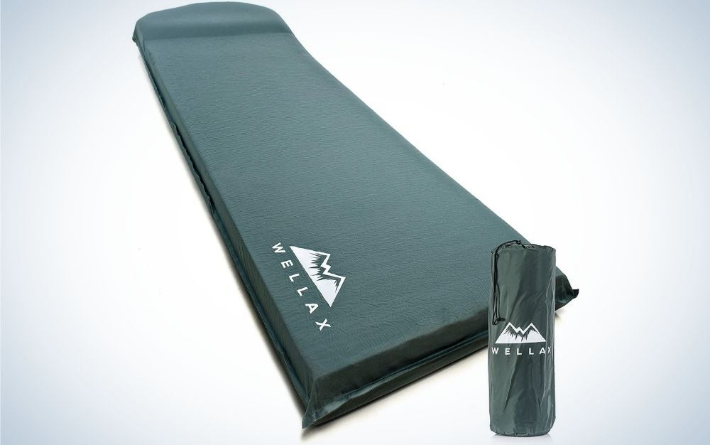 A black thick sleeping pad with the name of the firm WELLAX up to it and a black packing bag.