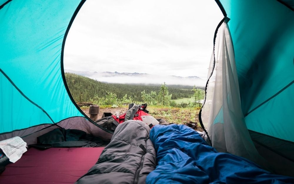Blue and gray summer sleeping bag inside tent
