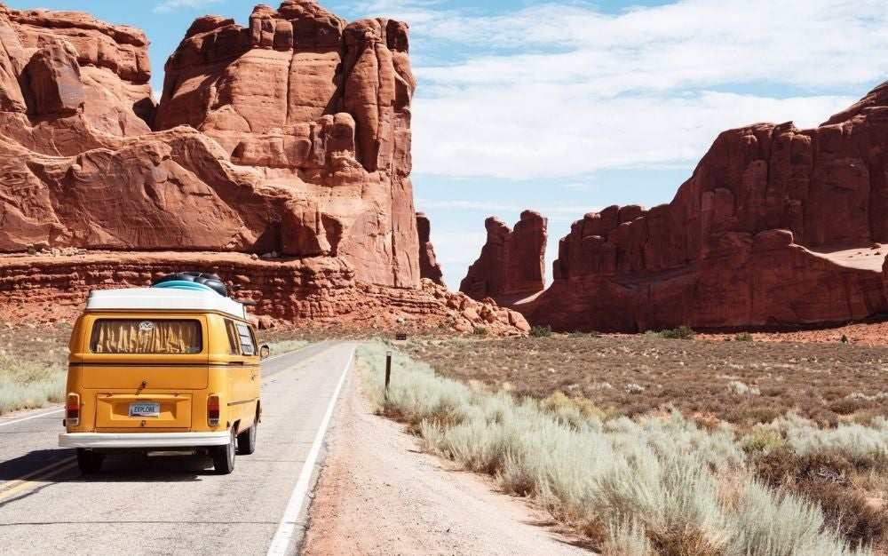 A yellow minibus traveling on open road between rocks and arches, sideways lush bushes.