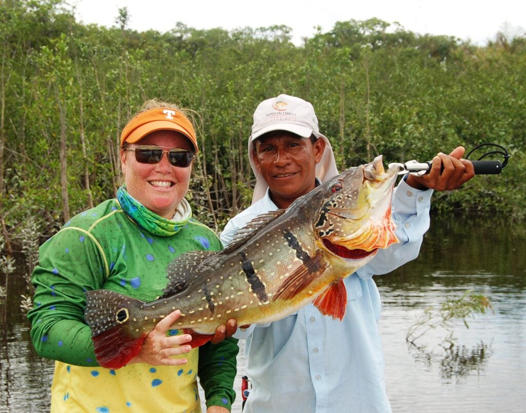 Anglers holding a large peacock bass.