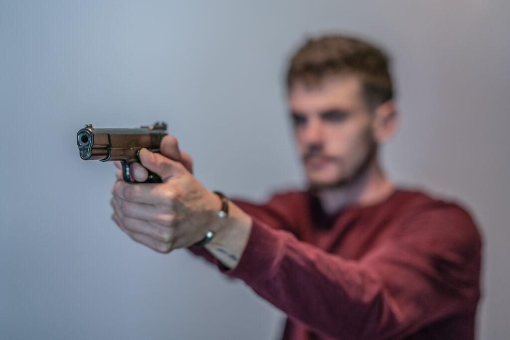 Batt Mann practices shooting a handgun.