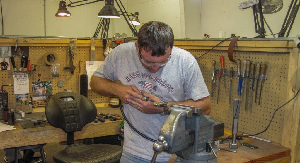 gunsmith working on a pistol in a vice.