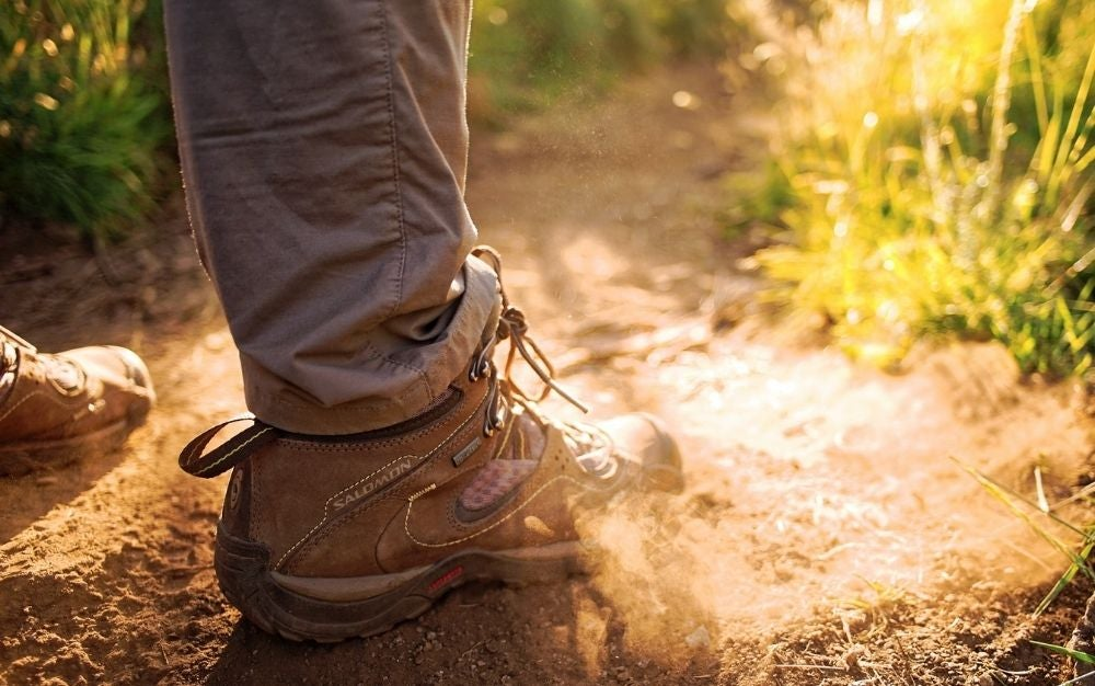 The foot of a man with a brown hiking shoe who has just stepped on a dusty spot in it.