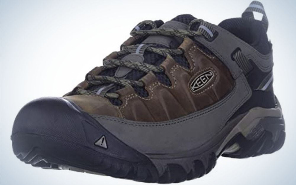 A thick and dark grey and brown men's winter shoes with thick black laces and a dark rubber with the KEEN logo on it.