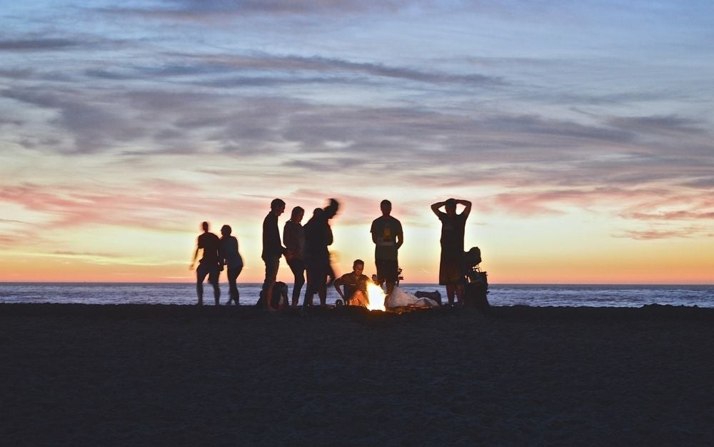 A group of people standing around a fire in the setting sun.