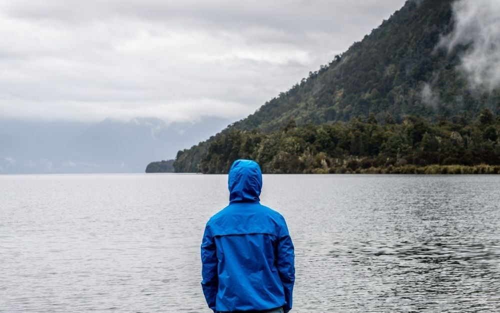 A man wearing a blue rainy jacket and standing in front of the big lake and under it the mountain.