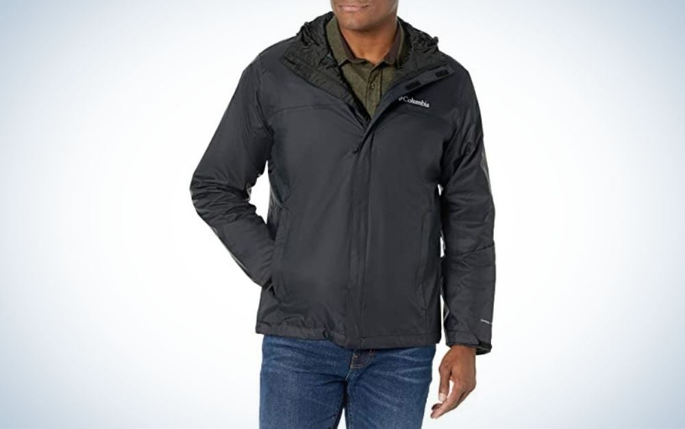 A man wearing and posing with a dark grey rain jacket and jeans.