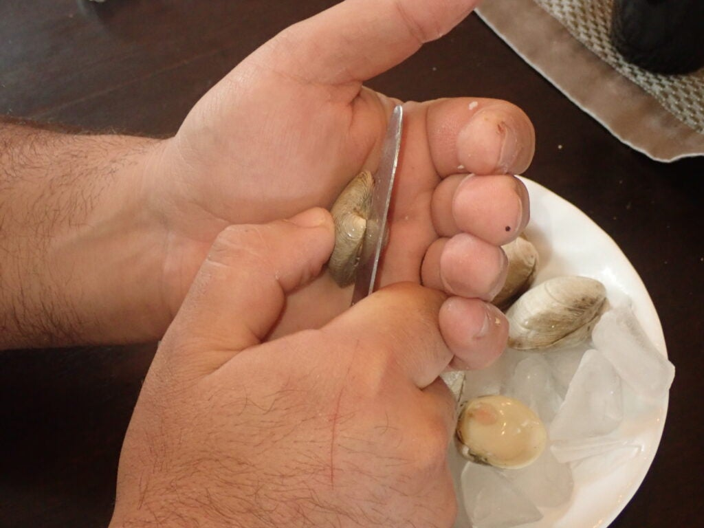 Opening clams with a knife.