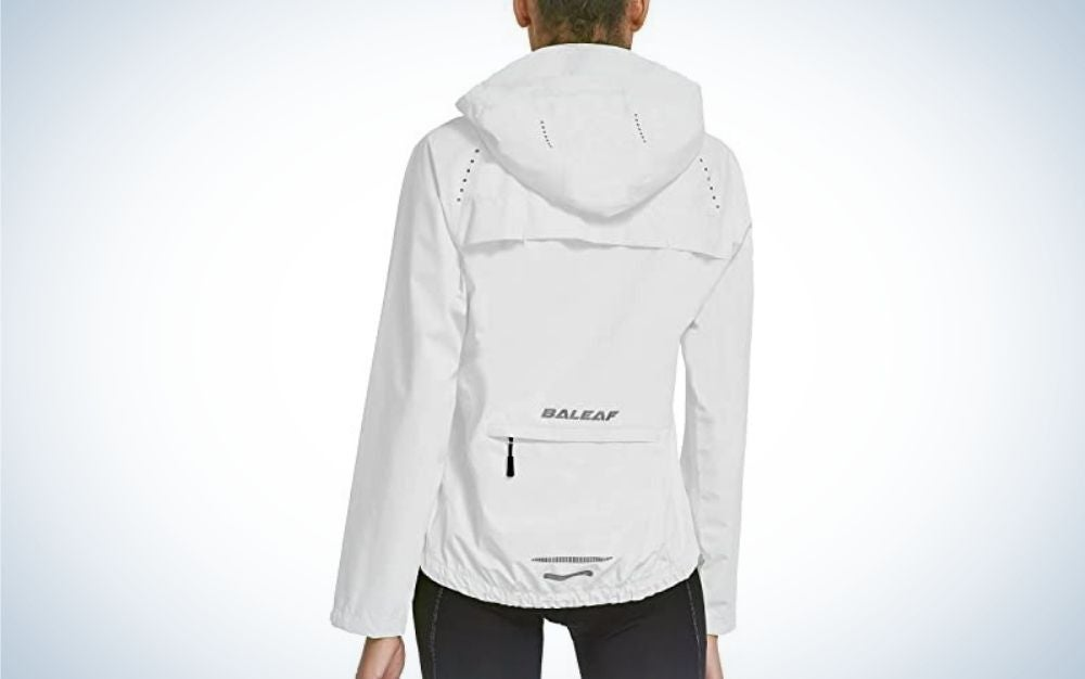 A woman on her back wearing a light white rainy jacket with a hood into it.