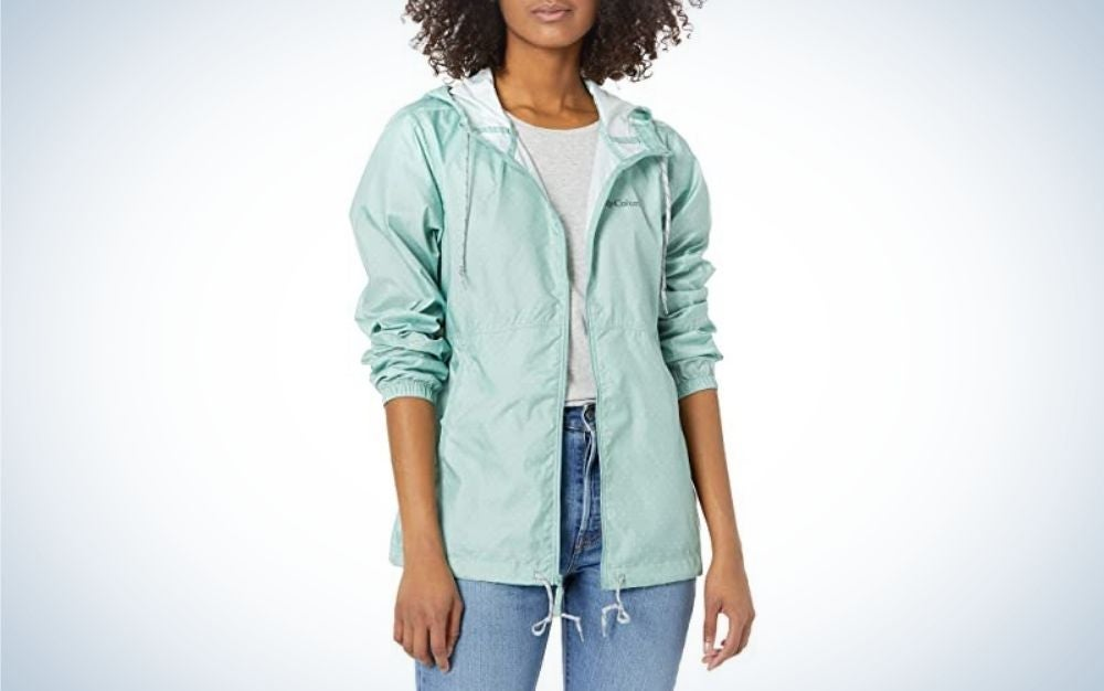 A woman posing with a light blue windbreakers jacket and wearing jeans too.