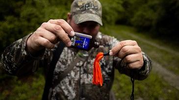 Hunter putting deer urine on drag rag.