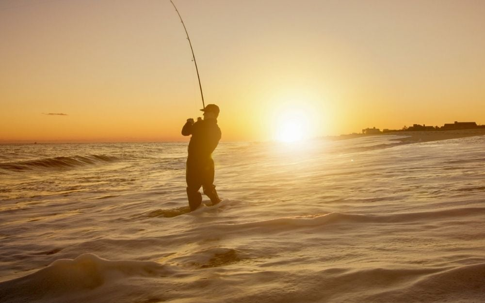 A man into the sea under the sunset with a fishing rolling reel in his hands fishing.