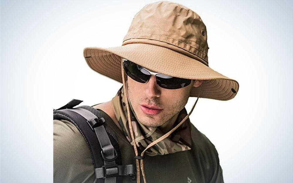 A young man with sunglasses wearing a beige hat.