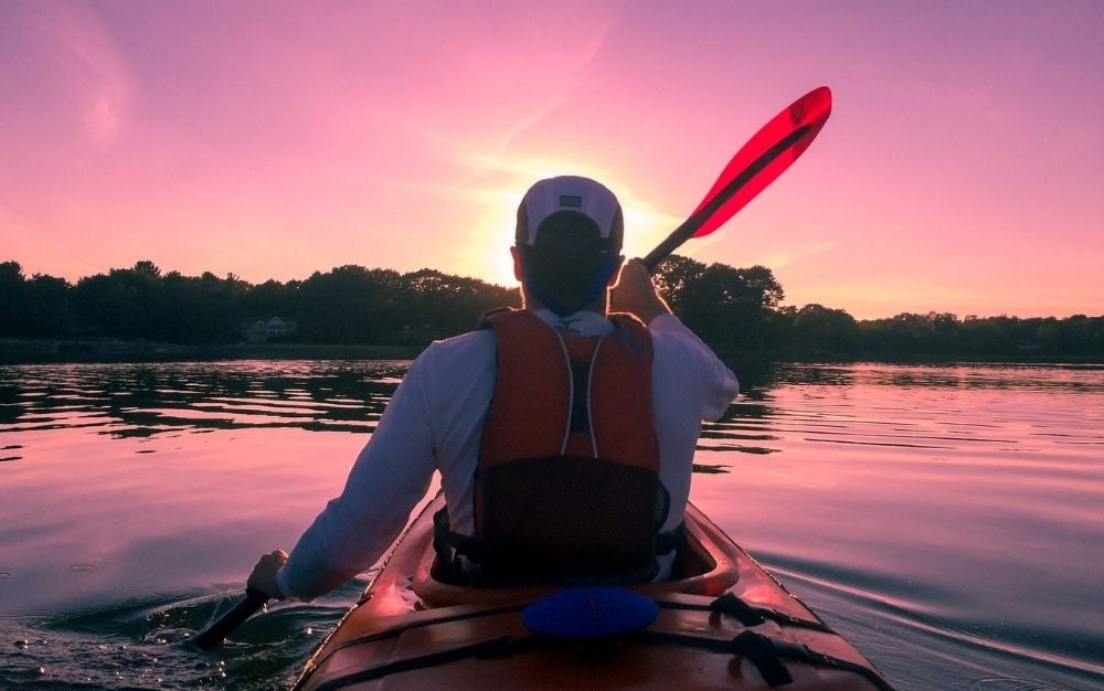 A man in a white t-shirt with a pedal in his hand who uses it to ride his kayak in the middle of the sea and under the setting sun.