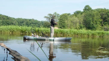 Man standing over the kayak and fishing to a lake.