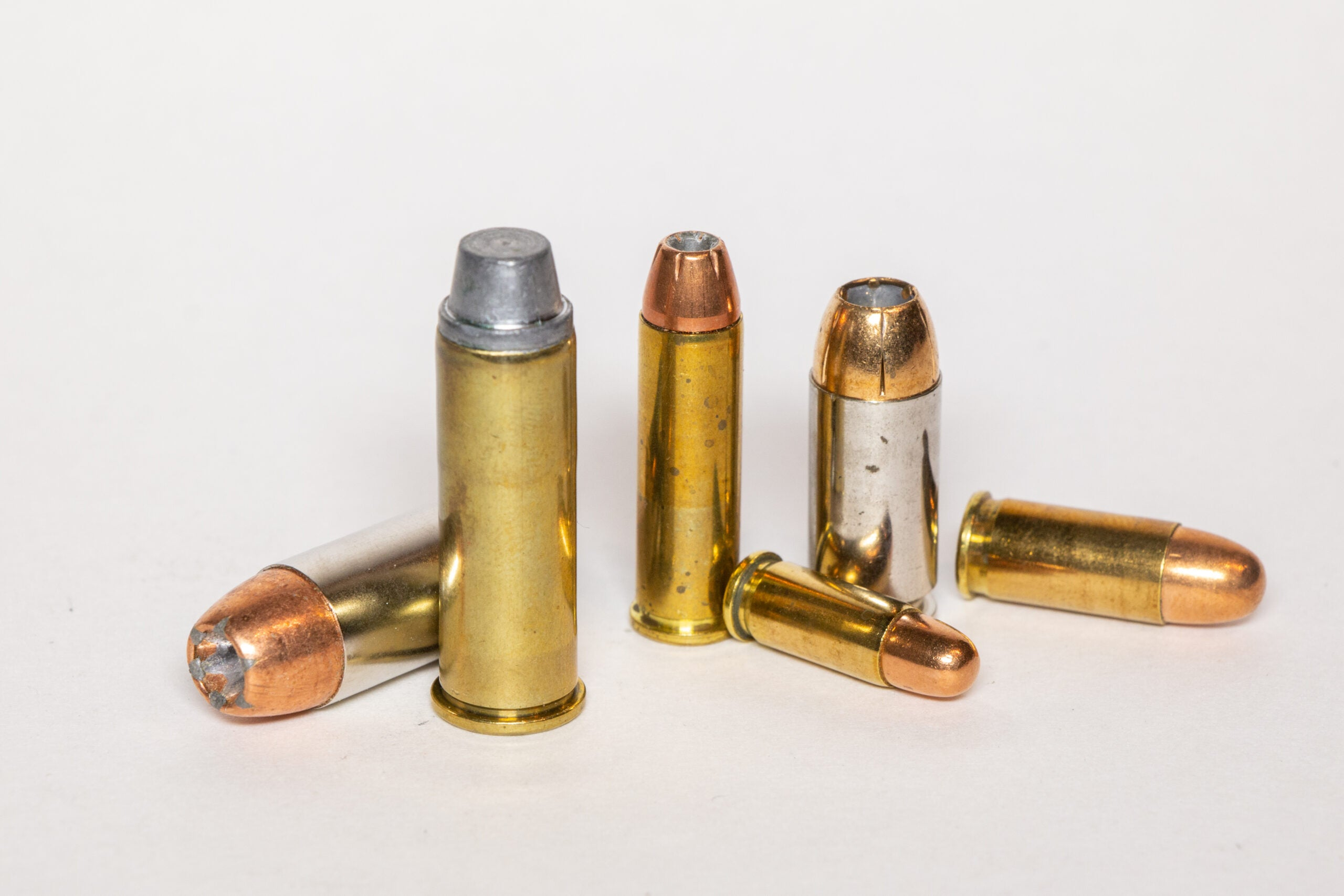 Six handgun cartridges on a white background.