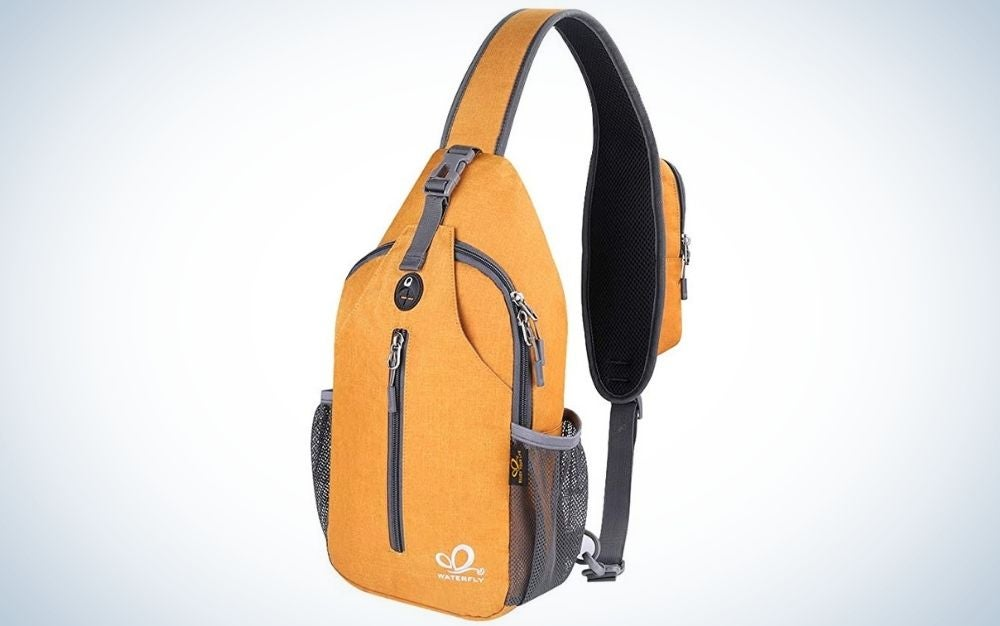 A yellow crossbody sling backpack sling bag travel hiking chest bag daypack with a center pocket with grey zipper.