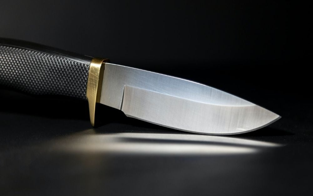 A sharpen knife standing on his curved tip with a black bottom and a gold line into it.