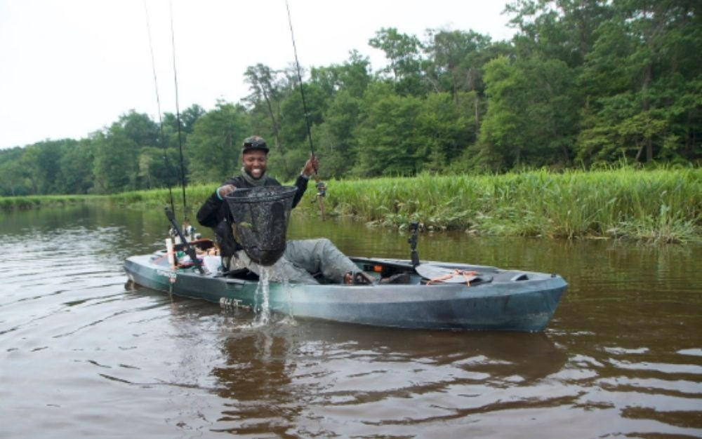 Fisherman with a net in the Old Town Topwater 120 kayak