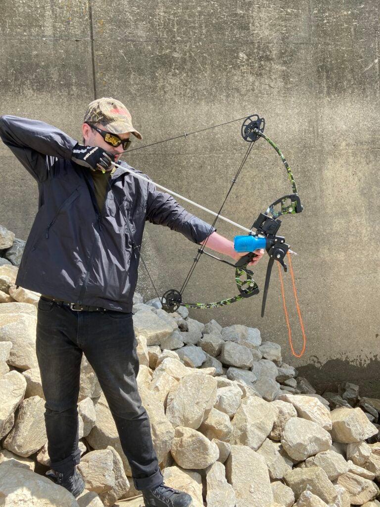 bowfisherman aims at invasive carp