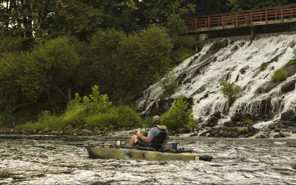 Person sitting on a Hobie kayak and fishing on the river.