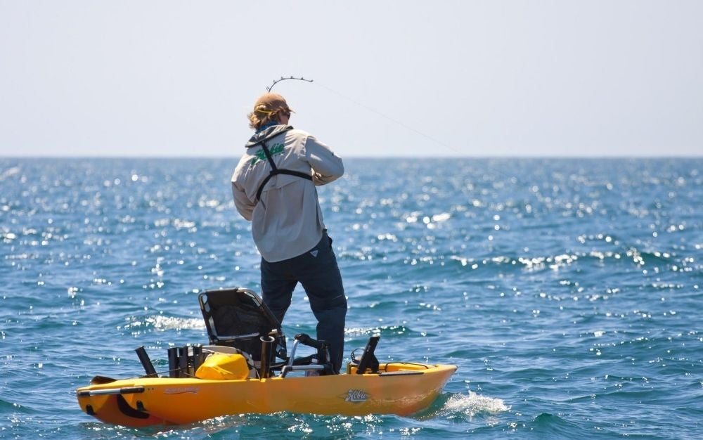 Person standing and fishing on the Hobie Pro Angler 12 kayak.