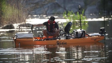 Fisherman holding a bass and rod while in fishing kayak.