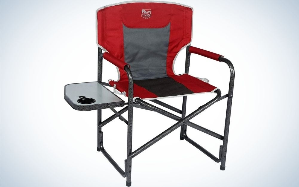A red chair with a table beside it with four portable legs and with a grey line leather in the middle of the chair.