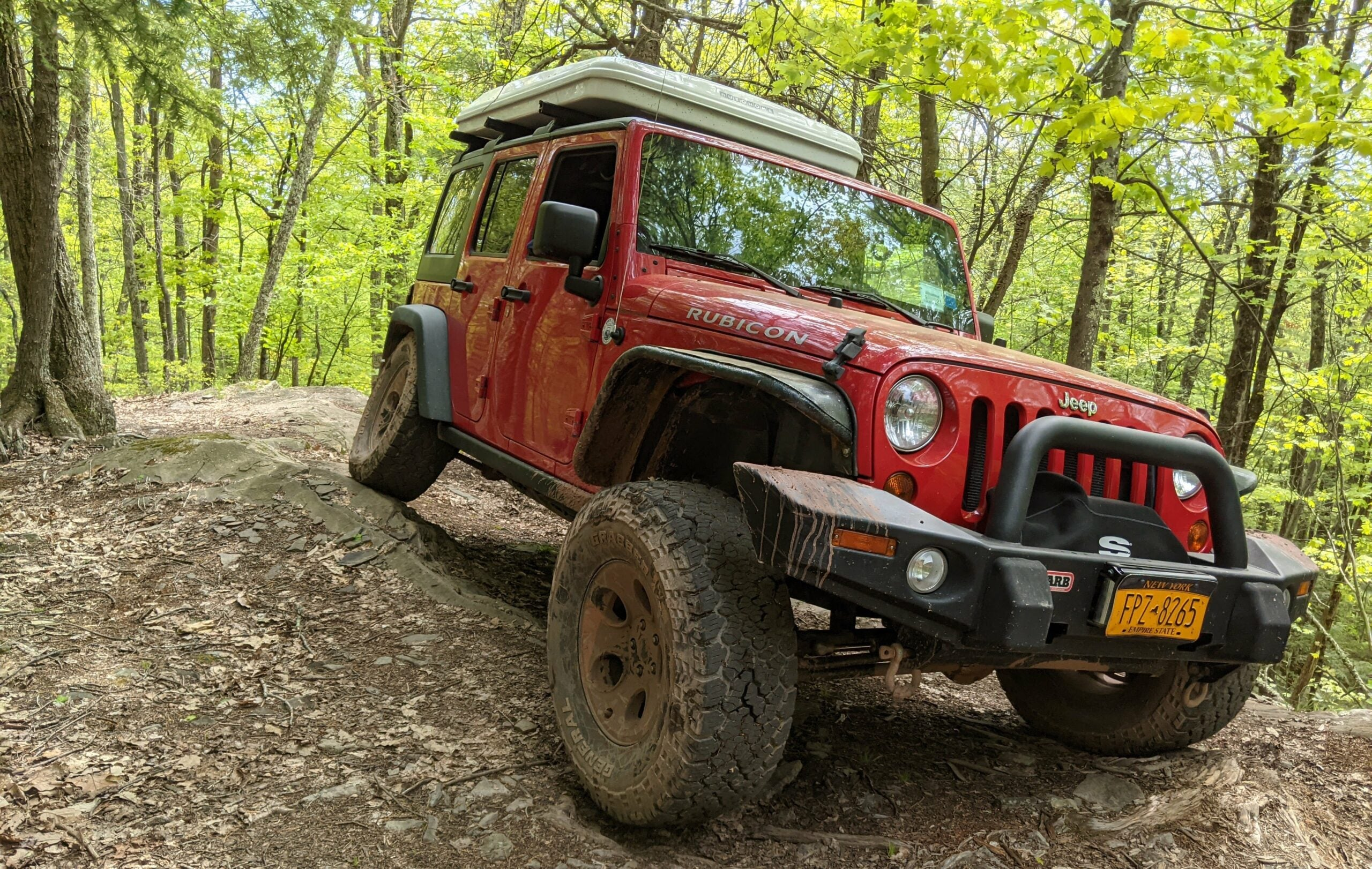 An overland jeep driving through the woods.