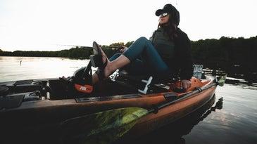 Woman on pedal kayak holding a fishing rod.