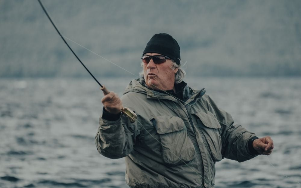A man wearing a grey jacket, a black hat and black sunglasses in the middle of the water with a fishing stick fishing.