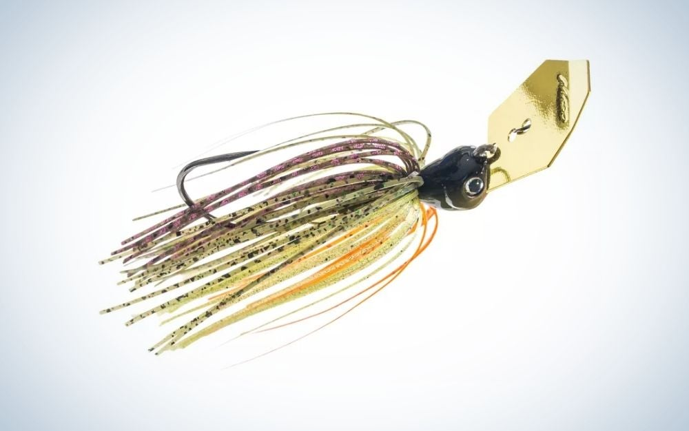 A fish bait with many colorful threads and a gold metal clip in it.